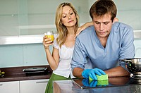 Young woman laughing at man using sponge in kitchen