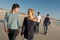 2 couples walking on the beach