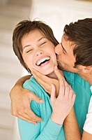 Portrait of man kissing smiling woman