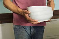 Young man carrying stack of plates