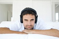 Young man lying on bed, listening to music with headphones