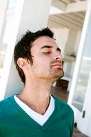 Portrait of a young man with eyes closed, leaning against terrace beam (thumbnail)