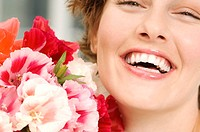 Portrait of smiling woman holding bunch of flowers