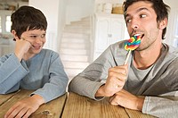Father eating lollipop with his son