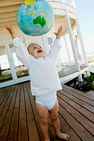 Little boy throwing inflatable globe in the air