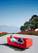 A man lounging on a couch in the road