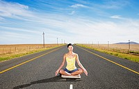 A woman doing yoga in the middle of the road