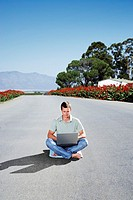 A man on a laptop in the middle of the road