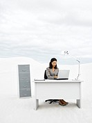 A businesswoman in the middle of nowhere at her desk
