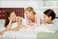 Three girlfriends talking in bed
