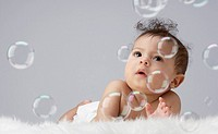 A baby surrounded by bubbles