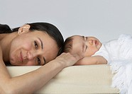 A woman lying beside a sleeping baby