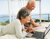 A couple on a laptop in their bedroom