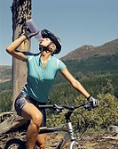 A woman drinking a bottle of water on her bike
