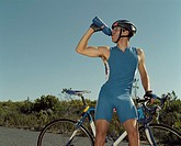 A cyclist having a drink of water on a rural road