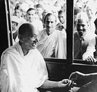 Mahatma Gandhi collecting funds for untouchables at a train station on his way to Assam, India