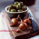 Shallots and green olives on chopping board