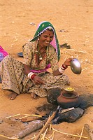 woman cooking food in desert , pushkar fair , rajasthan , india