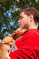 Side profile of a young man with a dog