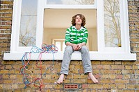 Teenage boy sat on windowsill