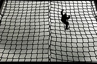 Silhouetted soldier climbing net