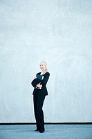 Businesswoman holding file against chest, laughing, full length portrait