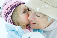 Toddler girl kissing grandmother on cheek, both dressed in winter clothing, close-up