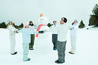 Young friends standing in circle around snowman, holding hands, smiling at camera