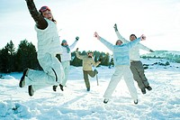 Young friends jumping in the air, dressed in winter clothing, smiling at camera