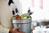 Waiter Carrying Bucket of Wine Bottles on Ice