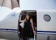 Young Woman Alighting from Private Jet