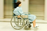 Woman using wheelchair, full length, blurred motion