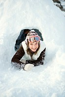 Teen girl crawling out of tunnel in snow