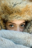 Preteen girl, wearing fur hat, looking over fur blanket, close-up