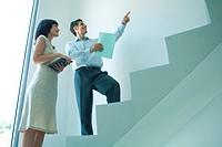 Businessman and young businesswoman standing on stairs, looking up, pointing