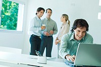 Businessman in office, using laptop computer, smiling, associates in background
