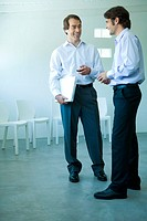 Two businessmen standing, looking at each other, full length
