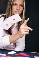 Woman playing poker throws away a perfect hand, pair of aces in the hole