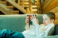 Boy reclining on couch, reading book