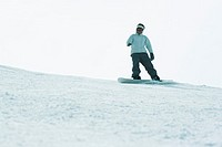 Young man snowboarding on top of ski slope, full length