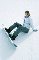 Young snowboarder sitting on the ground, looking at camera