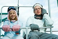 Young man using cell phone, sitting on chair lift with sister, both dressed in winter clothing