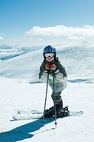 Young skier leaning on ski sticks, smiling at camera, full length portrait