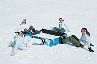 Four young snowboarders sitting on the ground in a square, looking at camera
