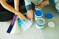 Couple sitting on floor, pointing to color swatches, cropped view