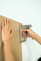 Woman stapling corrugated cardboard, cropped view of hands