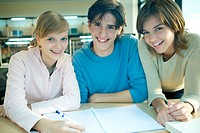 Three students studying together, smiling at camera