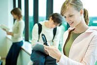 Female student looking at cell phone in front of window, smiling, students in background