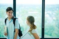 Two students in front of window, looking at each other, smiling