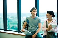 Two students chatting in front of window, smiling at each other